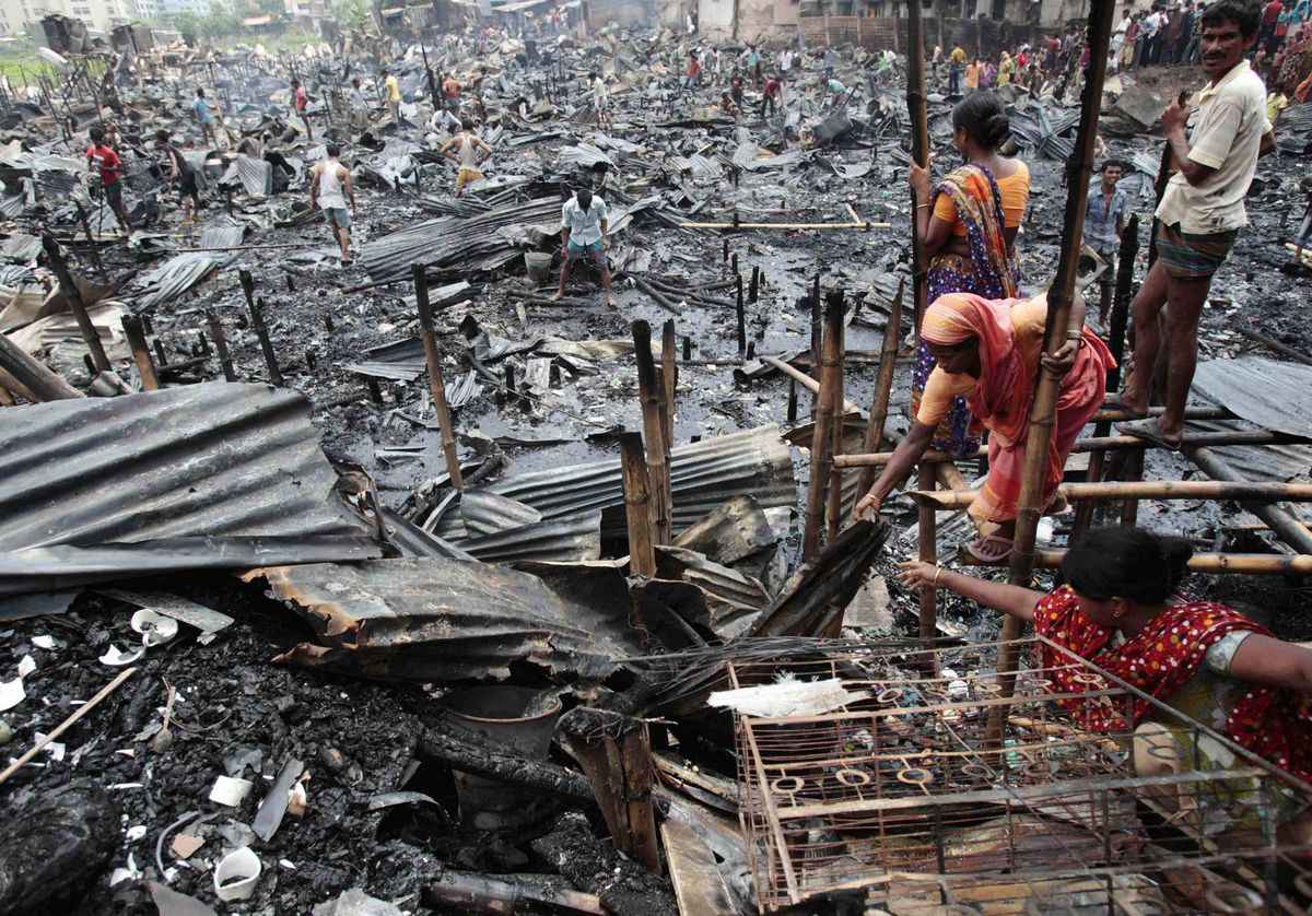Women try to salvage their belongings after a fire in a slum at Shyamoli in Dhaka, Bangladesh. At least 10 people were injured, including a fire fighter who sustained burn injuries, and more than 150 shanties were burned down as a blaze swept through a slum in the city's Shyamoli area, the local fire department said.