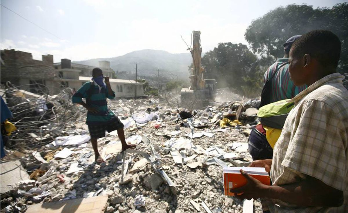 A crew uses an excavator to recover files from the collapsed building of Unibank, one of the biggest banks of Haiti, 12 days after the earthquake that devastated the city.