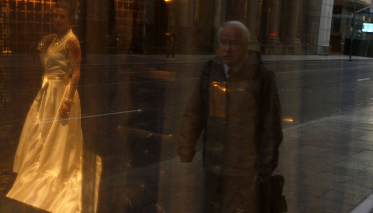 A man is reflected in a window as he walks in downtown Toronto.