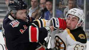 New York Rangers' Steve Eminger (44) is checked by Boston Bruins' Brad Marchand (63) during the first period of an NHL hockey game at Madison Square Garden, in New York, Monday, April 4, 2011. (AP Photo/Paul J. Bereswill)