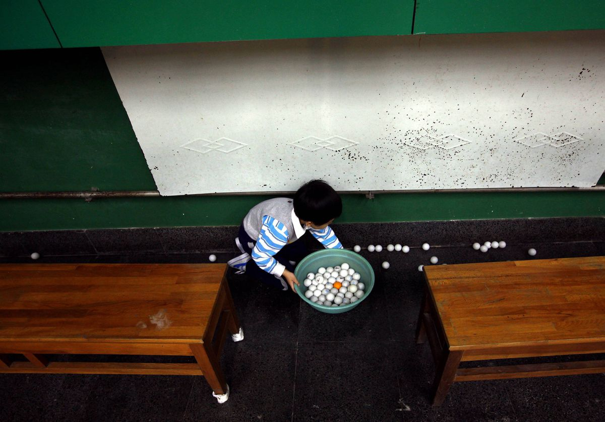 A young student collects table tennis balls during a class at the Shichahai Sports School in Beijing.