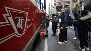 Customers board a Toronto Transit Commission streetcar at Yonge and Queen Streets in Toronto on November 28, 2011.