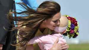 Catherine, the Duchess of Cambridge is presented with flowers and a hug by 6-year-old Diamond Marshall on arrival with Prince William at Calgary International Airport in Calgary on July 7, 2011.