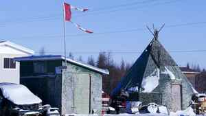 A tattered flag flies over a building in the impoverished first nations community of Attawapiskat.