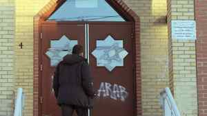 A man looks at new vandalism on the front door of the Outaouais Islamic Centre in Gatineau , Quebec on Thursday, Jan. 5, 2012.