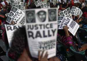 Residents use images of black teenager Trayvon Martin to block the sun while taking part in a rally demanding justice for his killing in Miami, Florida April 1, 2012.