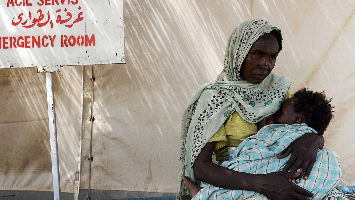 A displaced Sudanese woman waits for a medical checkup with her baby in front of an emergency service at the Turkish Red Crescent Hospital in the city of Nyala, the capital of South Darfur state in the western part of the Sudan, 03 August 2007.