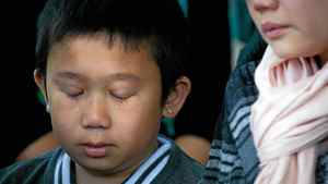 Ten-year-old Eric Ut, son of deceased Langley mushroom farm worker Ut Van Tran, cries as his mother, Hong Dang, speaks to reporters at an inquest into the 2008 deaths and injuries on the farm, in Burnaby, B.C., on May 10, 2012.