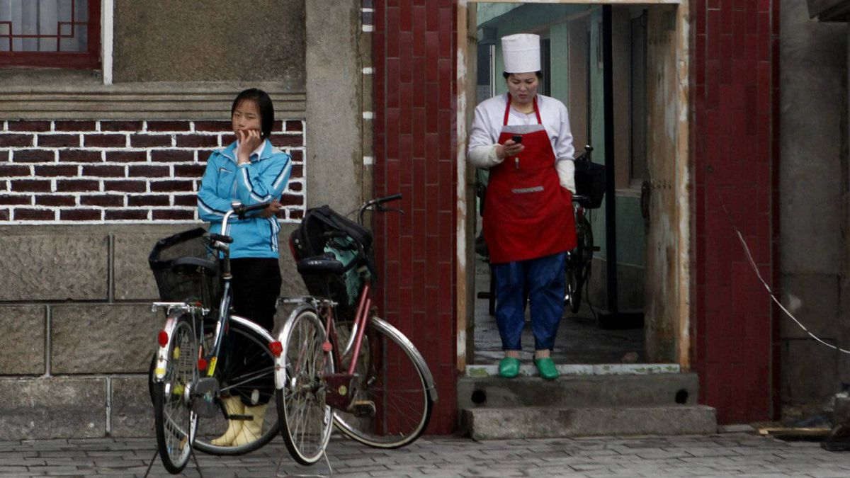 A North Korean cook checks her mobile phone in Kaesong, North Korea, Monday, April 23, 2012. North Korea has two types of mobile user. In the northern border areas, people use Chinese phones, which enable them to call abroad. Friends or fixers in China pay the bills. Far more widely used are the phones operated by Egypt's Orascom, which cannot take international calls, but do aid the spread of information around the country.