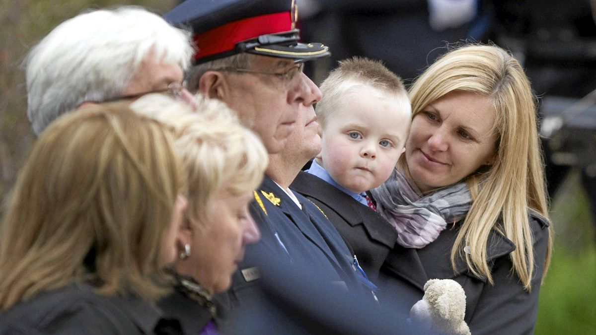 Christine Ryan, wife of slain Toronto police officer Sergeant Ryan Russell, holds their 2-year-old son Nolan while attending the 12th annual Ceremony of Remembrance for Ontario's police officers lost in the line of duty at Queen's Park May 1, 2011.