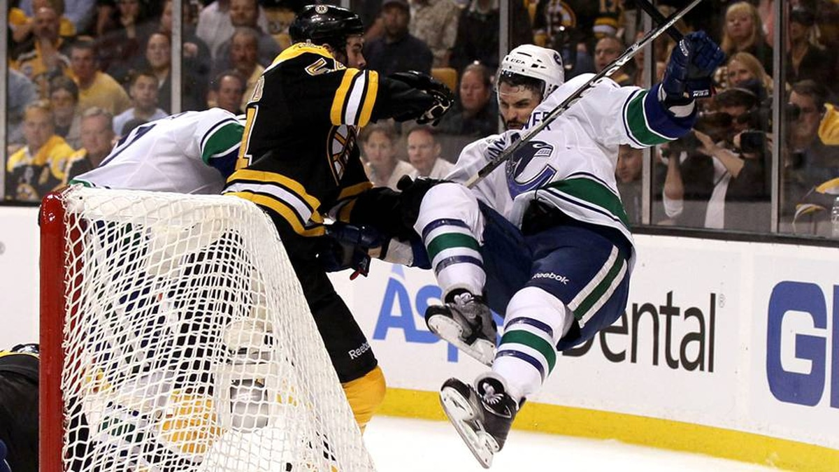 Adam McQuaid of the Boston Bruins checks Maxim Lapierre of the Vancouver Canucks during Game 6.