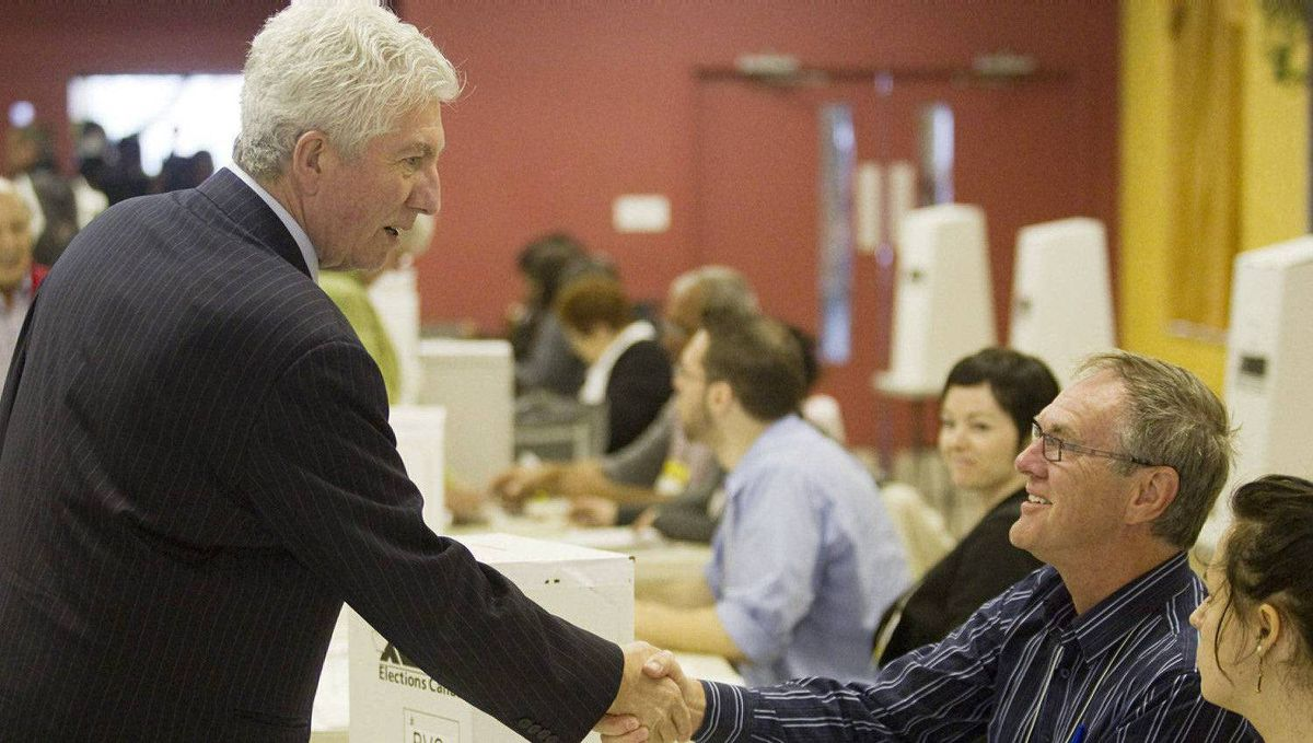 Bloc Quebecois Leader Gilles Duceppe, left, shakes hands with election workers after he casted his ballot Monday, May 2, 2011 in Montreal Que. Canadians are going to the polls on in a general.