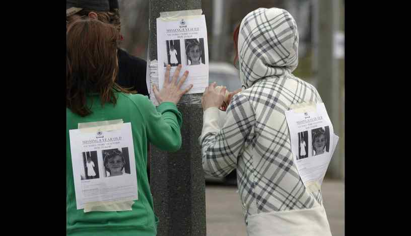 "Cassandra Craig and Shiloh Roth hang a poster for then-missing Victoria ""Tori"" Stafford, 8, on a street corner in Woodstock, Ont. on Friday April 10, 2009."