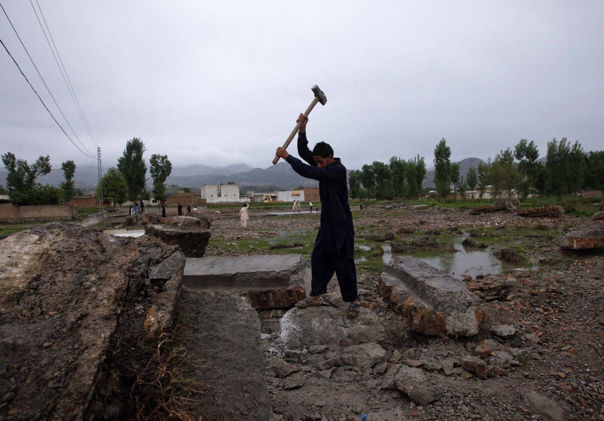 Yasir, 12, uses a hammer to break a concrete block to scavenge for iron from the demolished compound of Osama bin Laden in Abbottabad, Pakistan.
