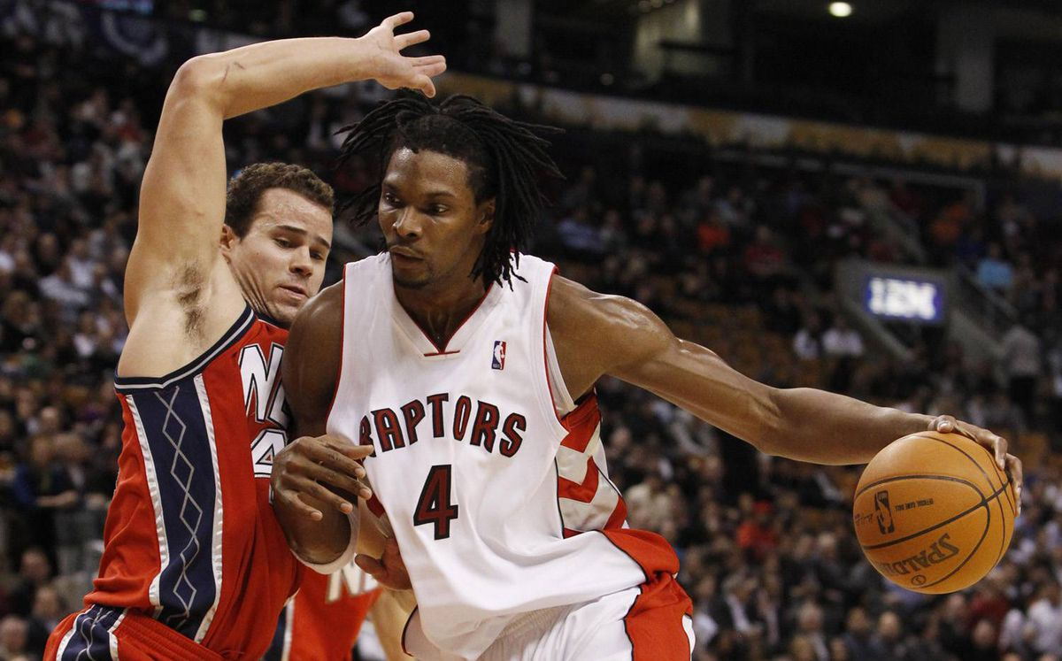 Toronto Raptors' Chris Bosh goes to the net against New Jersey Nets' Kris Humphries, left, during the first half of their NBA basketball game in Toronto, February 3, 2010.
