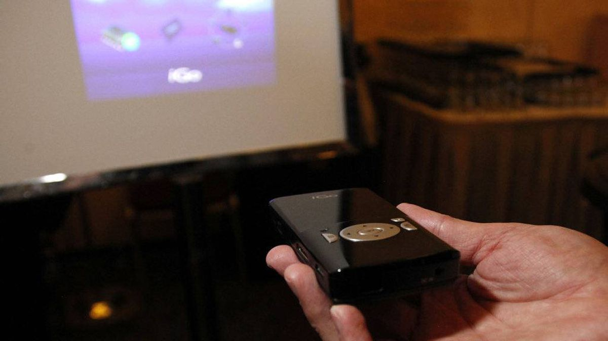 A man demonstrates the iGo Pocket Projector UP-2010 at a preview of the Consumer Electronics Show (CES) in Las Vegas January 4, 2011. The projector has a microSD slot so that a user can display photos or videos shot with a cell phone and stored on a card.