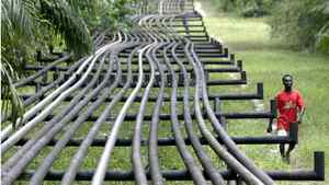 In this file photo, an unidentified man walks along oil pipelines belonging to Italian oil company Agip in Obrikom, Nigeria on Monday, March 6, 2006.