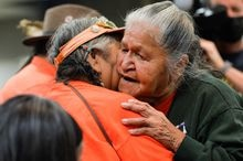 Residential school survivor Evelyn Camille is embraced at a presentation of the findings on 215 unmarked graves discovered at Kamloops Indian Residential School in Kamloops, British Columbia, Canada, July 15, 2021.  REUTERS/Jennifer Gauthier
