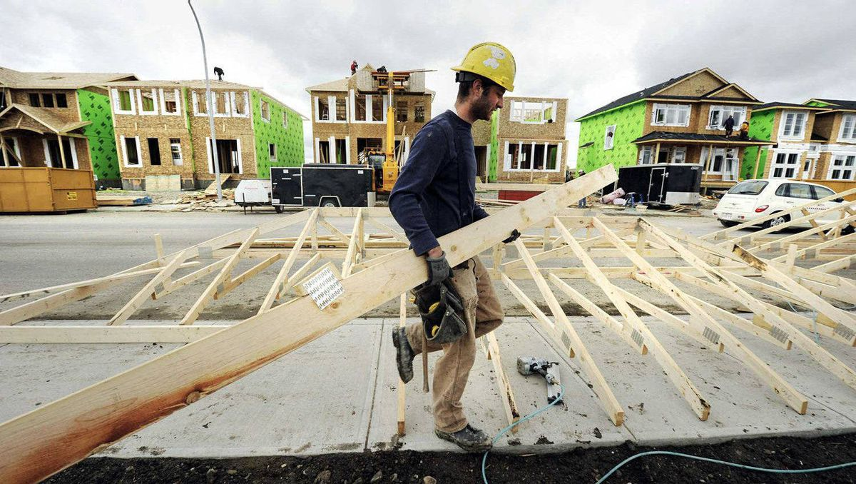 A construction worker works on building new homes in Calgary, Alberta.