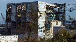 The Unit 4 reactor building at the crippled Tokyo Electric Power Co. (Tepco) Fukushima Dai-Ichi nuclear power station is seen through a bus window in Okuma Town, Fukushima Prefecture, Japan, on Saturday, Nov. 12, 2011. Tepco is struggling to contain the worst nuclear disaster in 25 years.