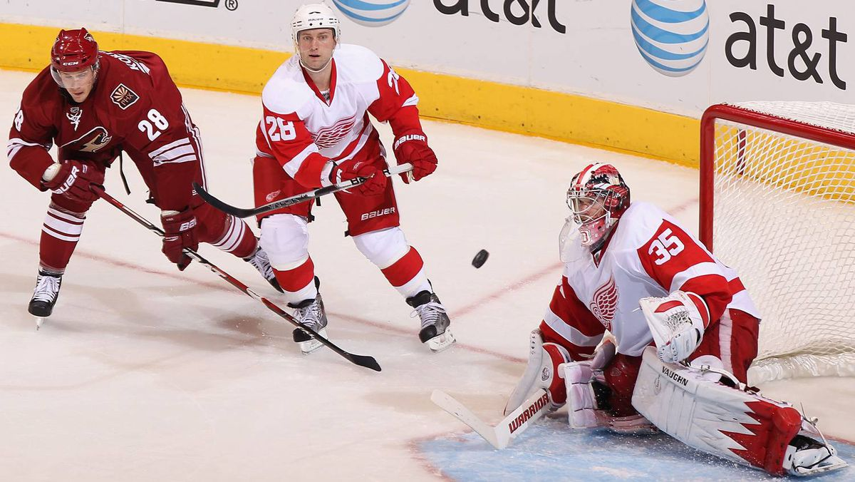 Brian Rafalski of the Detroit Red Wings clears the puck past goaltender Jimmy Howard while pressed from Lauri Korpikoski of the Phoenix Coyotes.