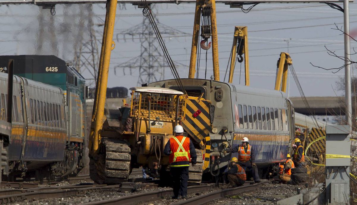 BURLINGTON, ONT. - Feb. 27, 2012 - A VIA passenger train passes crews working to get derails train cars back up onto the tracks in Burlington on Monday, Feb. 27, 2012. The Via passenger train, enroute from Niagara Falls to Toronto, derailed on Sunday at approximately 3:30pm. Three VIA employees in the engine died as a result if the crash, and many passengers were taken to local hospitals; three with serious injuries. One track has been open and trains have been passing the site all day. (Photo by Peter Power/The Globe and Mail)pmp