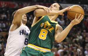 Utah Jazz forward Deron Williams is fouled by Toronto Raptors guard Jose Calderon during the first half of their NBA basketball game in Toronto March 24, 2010.