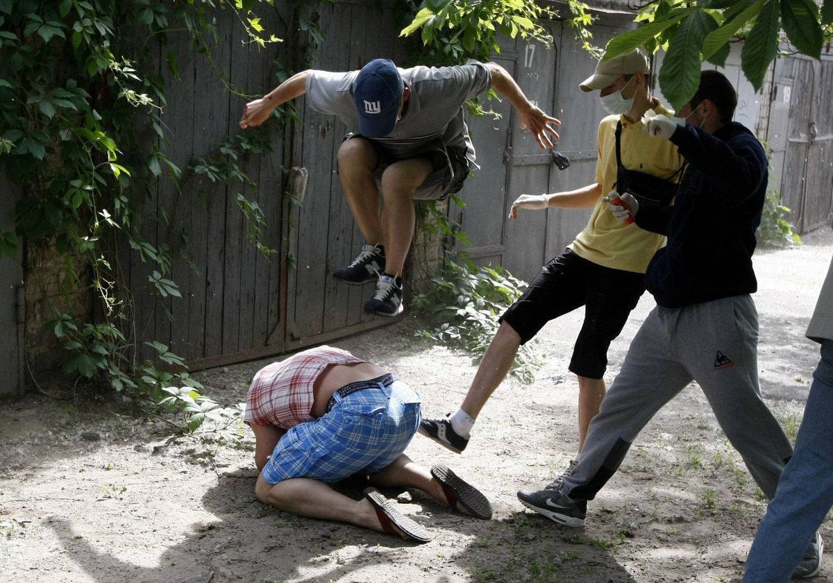 Unidentified people beat Svyatoslav Sheremet (L, bottom), head of Gay-Forum of Ukraine public organization, in Kiev, May 20, 2012. Sheremet was attacked after meeting with members of the media to inform them that a scheduled gay parade was cancelled. The attackers ran off when they realised members of the media were documenting the attack.