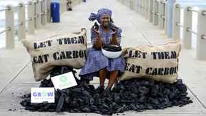 "An activist of British charity Oxfam pretends to eat a piece of coal as a protest aimed at 17th Conference of the Parties (COP17) under the UN Framework Convention on Climate Change (UNFCCC) as she sits between bags reading ""Let Them Eat Carbon"" Dec. 9 in Durban."
