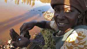 At the Barrick gold mine at North Mara, Tanzania, a woman pours mercury into her palm. She mixes the mercury with water and rock fragments to seek gold from bits of waste rock at the Barrick mine. Hundreds of local men and women invade the mine every day, seeking pieces of waste rock that might contain gold. Barrick is investigating allegations that about 10 women who trespassed on the mine were sexually assaulted by about a dozen Barrick security guards and Tanzanian police.