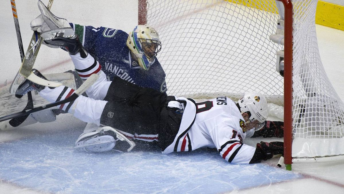 Chicago Blackhawks Jonathan Toews crashes into Vancouver Canucks goalie Roberto Luongo. REUTERS/Andy Clark