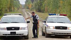 RCMP officers block the road near the entrance to a property of interest as police continue the investigation into missing St. Albert couple Lyle and Marie McCann in this September 2010 file photo.
