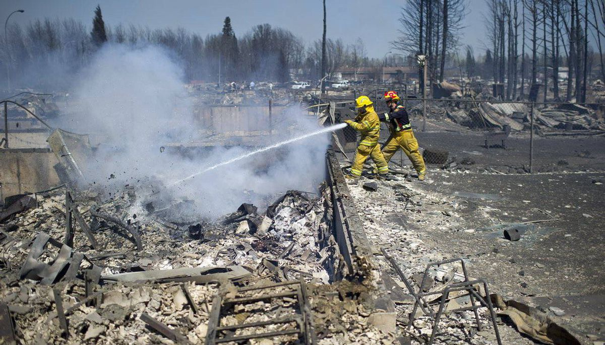 Firefighters put out hot spots after a forest fire hit the community of Slave Lake, Alberta.