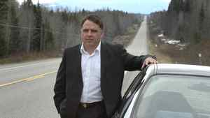 Prince George City Councillor, Brian Skakun with his car on a long strech of Highway 16 East near Prince George as a fuel transport truck passses by.