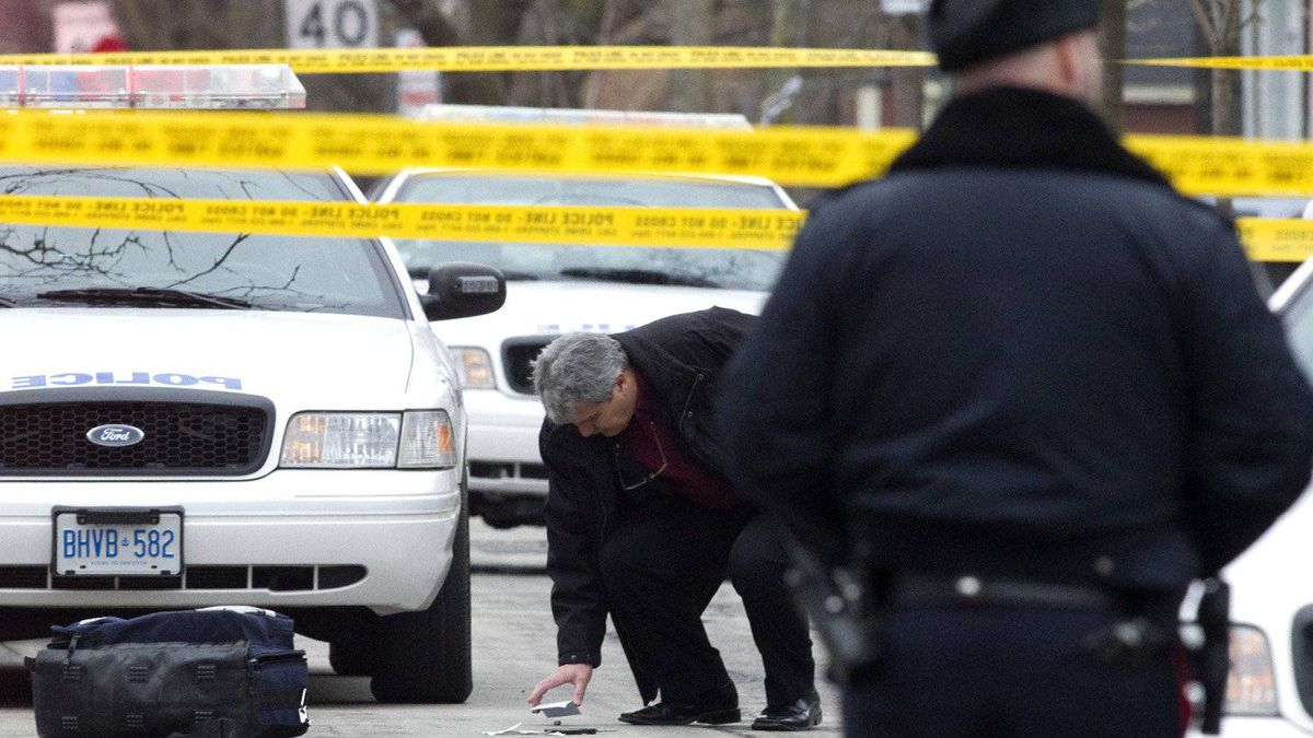 A member of the Police Special Investigations Unit inspects a used shell casing after Michael Eligon was fatally shot by the Police after allegedly threatening officers with scissors in Toronto on Friday February 3, 2012.