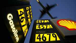 Gasoline prices are advertised at a gas station near Lindbergh Field as a plane approaches to land in San Diego, California, in this file picture taken June 1, 2008.