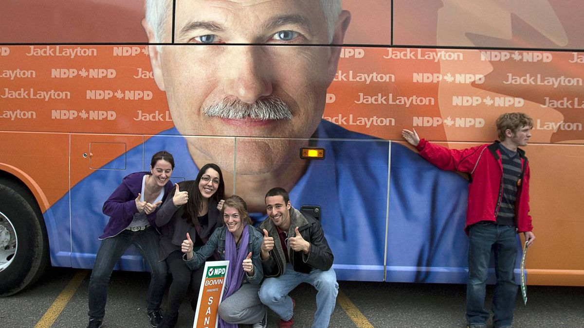 Supporters pose for photos by NDP Leader Jack Layton's campaign bus at a campaign rally at Ecole secondaire du Versant in Gatineau, Que.