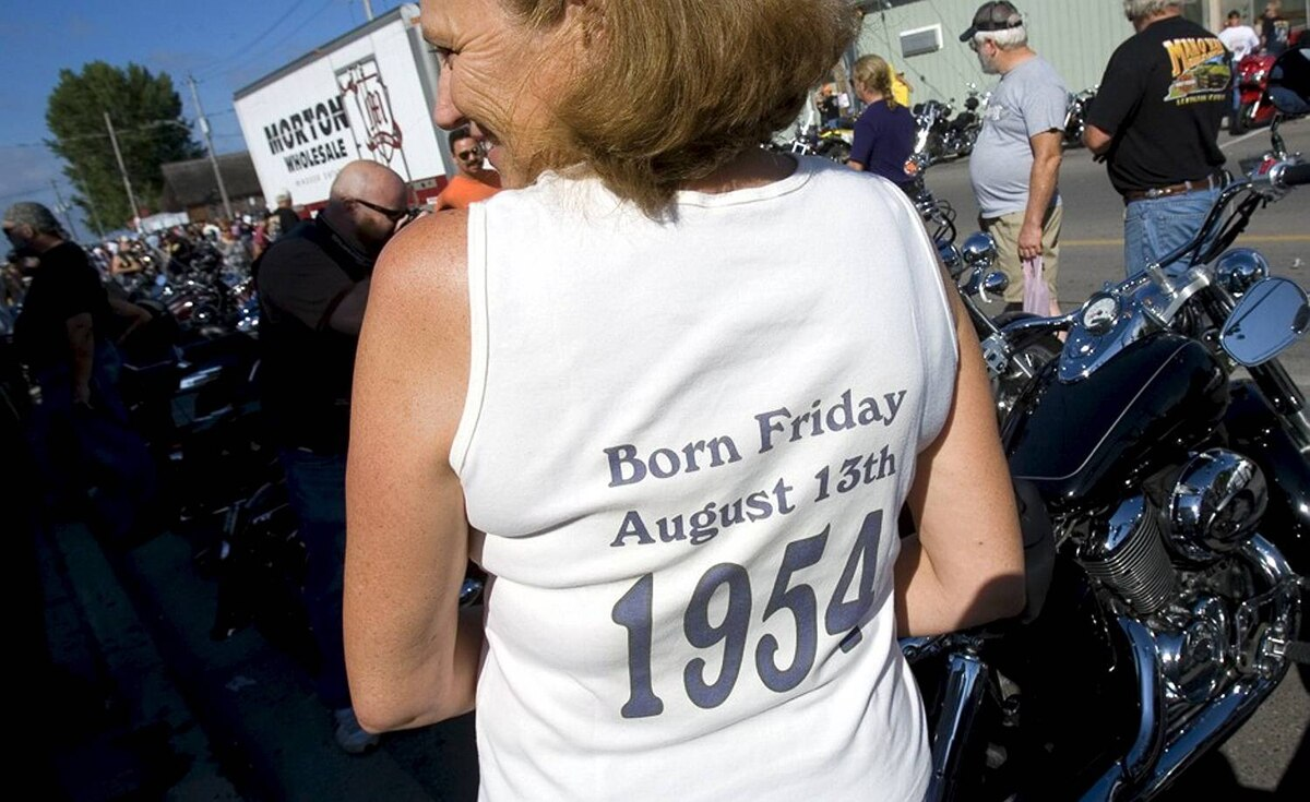 Thousands of bikers and fans of bikes, and those just wanting to view the spectacle descended upon Port Dover, Ontario for the 50th Friday the 13th Ride to Port Dover. Christine Nowak , of Woodstock, celebrating her birthday with a trip to Port Dover, wears a t-shirt that states her birth date quite plainly.