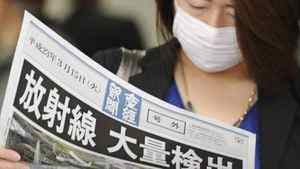 """A masked woman reads an extra newspaper with the banner reading, """"Radiation Detected in Large Amount,"""" at Osaka, western Japan, on Tuesday March 15, 2011."""