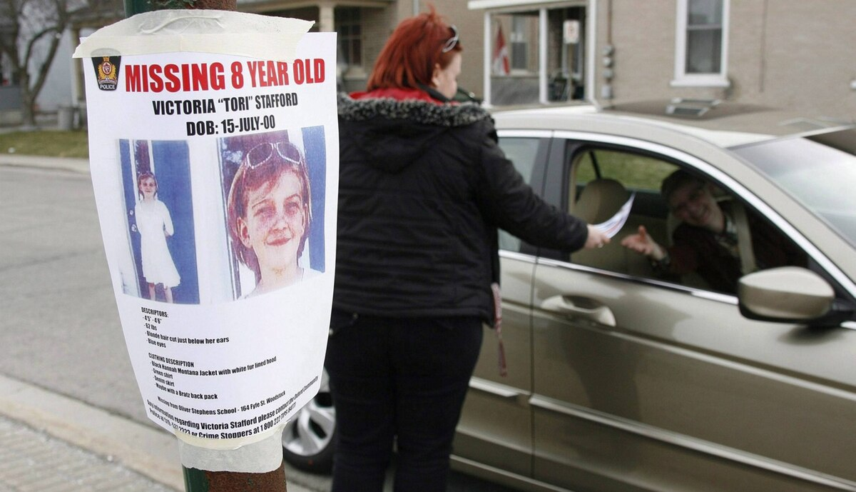 "Tiffany Ackers hands out a poster for then-missing Victoria ""Tori"" Stafford, 8, on a street corner in Woodstock, Ont. on Friday April 10, 2009."