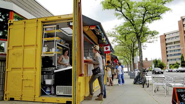 Vendors sell food out of shipping containers that have been transformed into micro-stores outside of the Scadding Court Community Centre in Toronto on May 30, 2012.