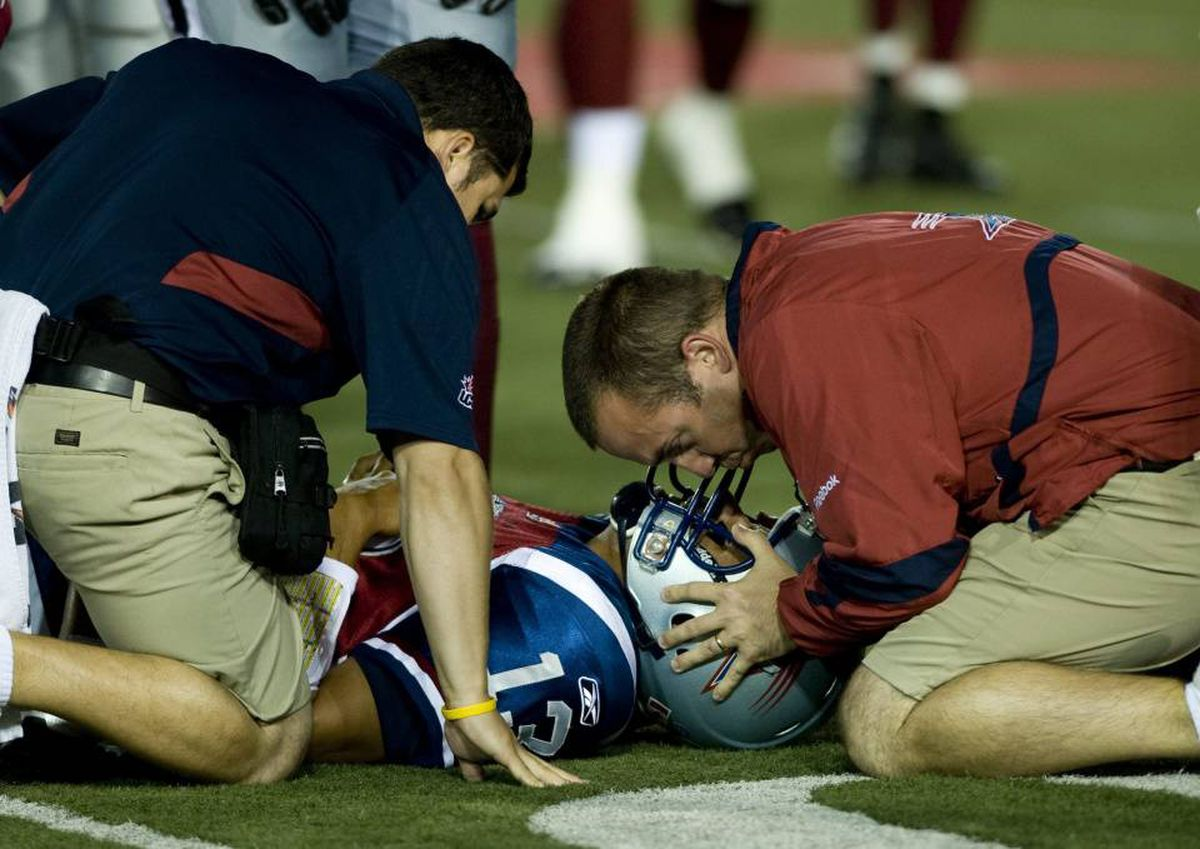 Montreal Alouettes quarterback Anthony Calvillo lies injured after being tackled by Winnipeg Blue Bombers' Odell Willis (not shown) during first half CFL football action in Montreal, Thursday, August 19, 2010.