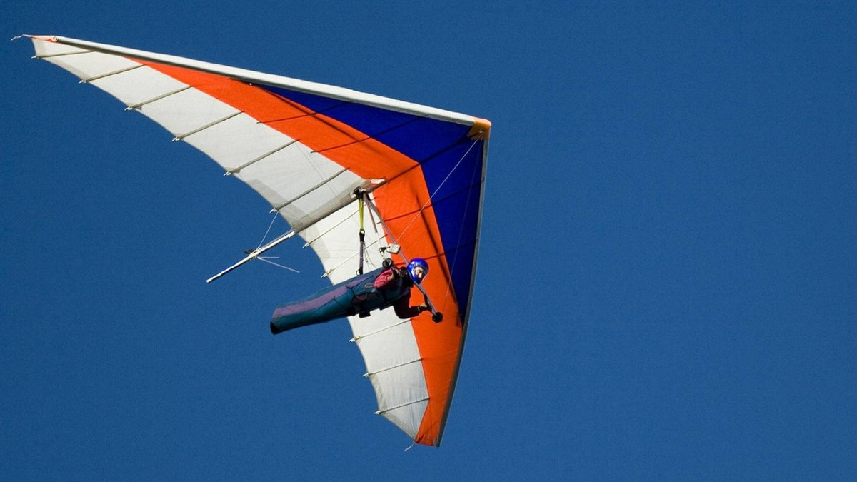 A hang-glider against a blue sky.