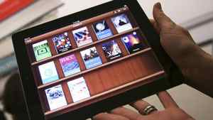 A woman holds up an iPad with the iTunes U app after a news conference introducing a digital textbook service in New York in this January 19, 2012, file photo.