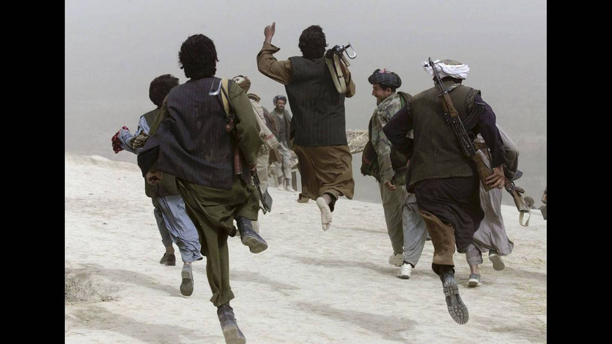 Afghan opposition Northern Alliance soldiers run and jump as they return from a front line position after battle near the town of Charatoy in the north of Afghanistan, October 10, 2001.