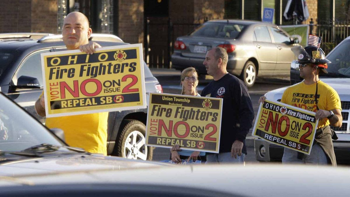 A group of fire fighters urge passing motorists to vote no on Issue Two in Tuesday's election, Monday, Nov. 7, 2011, in Cincinnati, near a hotel where Ohio Gov. John Kasich spoke in support of the issue.