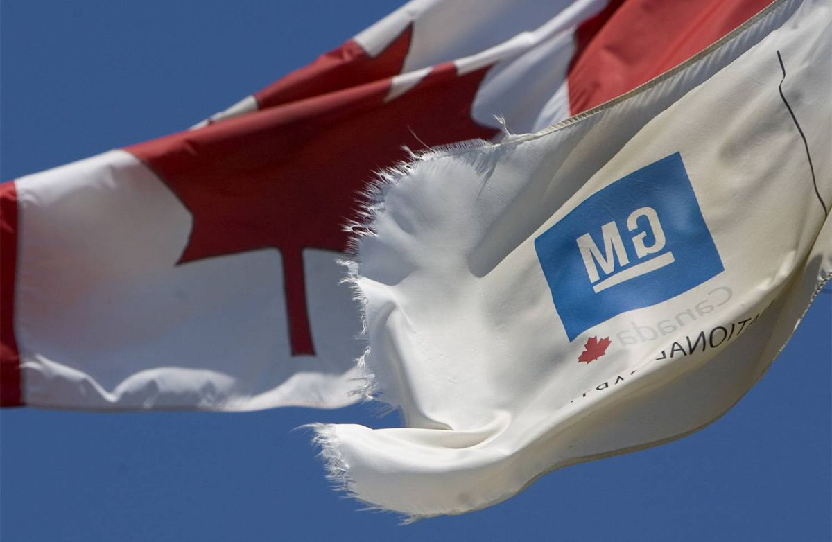 A tattered GM flag flies in front of a Canadian flag outside the General Motors plant in Oshawa, Ont.