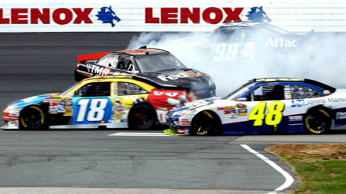 Denny Hamlin, driver of the No. 11 FedEx Small Business Toyota spins out behind Jimmie Johnson, No. 48, and Kurt Busch, No. 18, during the NASCAR Sprint Cup Series Sylvania 300 at New Hampshire Motor Speedway on September 19, 2010 in Loudon, New Hampshire.