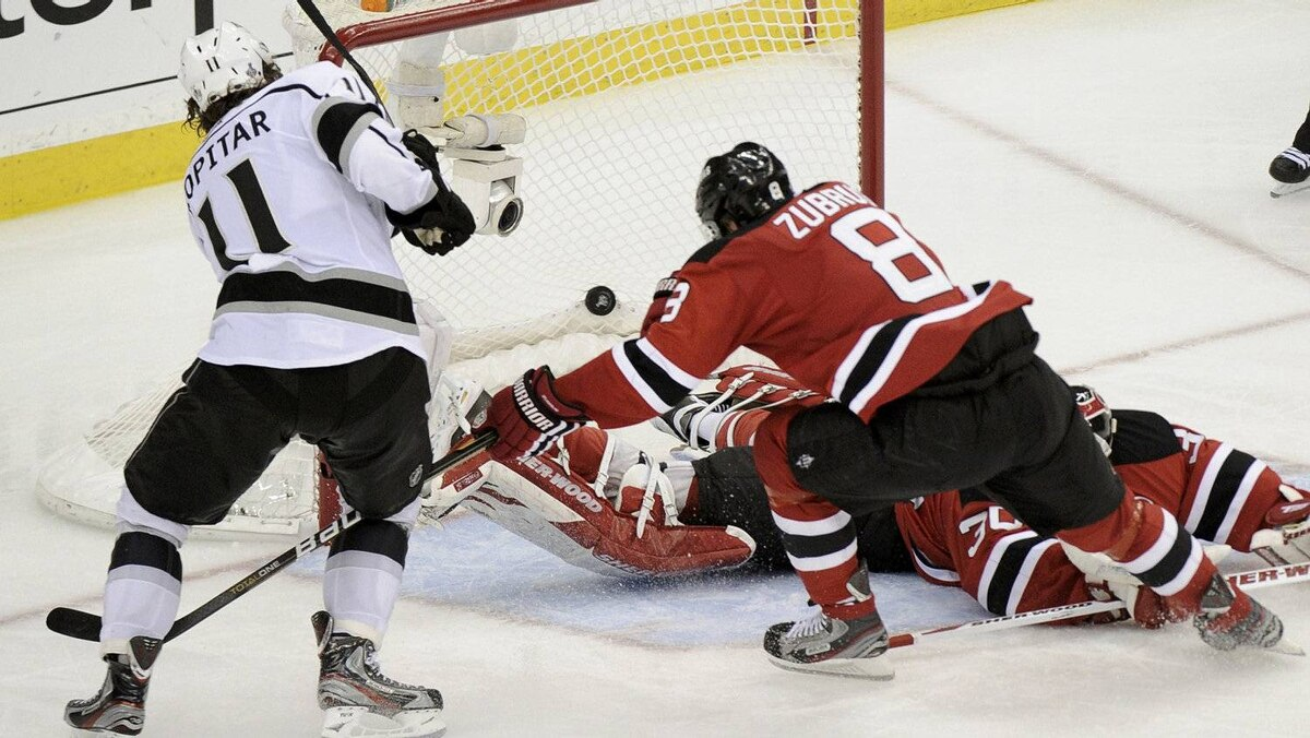 Los Angeles Kings' Anze Kopitar (L) scores on New Jersey Devils goalie Martin Brodeur as Devils' Dainius Zubrus tries to cover the play during overtime in Game 1 of the NHL Stanley Cup hockey final in Newark, New Jersey, May 30, 2012.