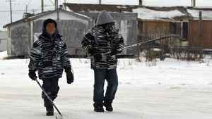 Two boys walk past substandard housing on their way to play hockey in Attawapiskat on Dec. 17, 2011